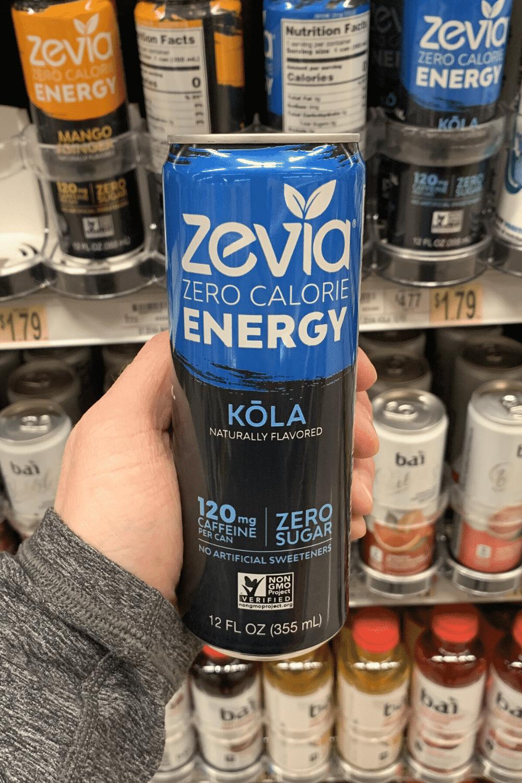 A hand holding a can of Kola flavored Zevia energy