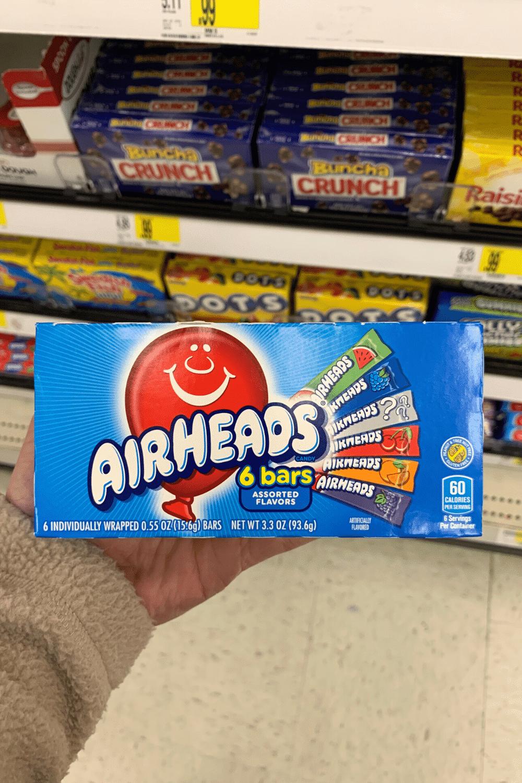 A hand holding a box of Airhead bars