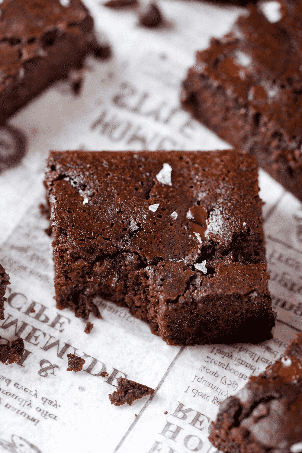 A brownie with a bite out of the one corner. The brownies is on a piece of white newspaper.