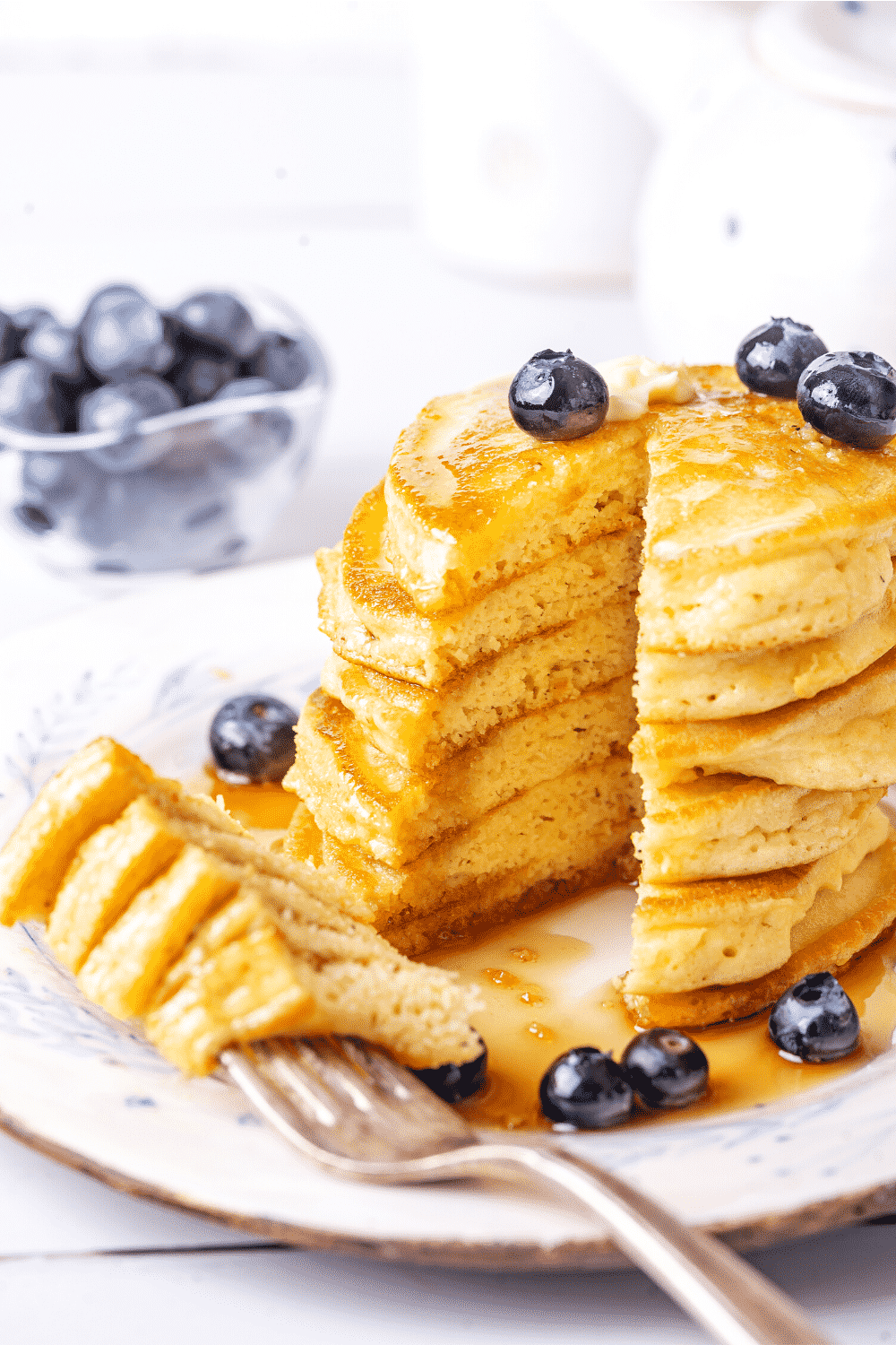 A stack of six pancakes on a plate with a slice of all six pancakes out of the front of the stack. A fork has the slice of the six pieces of pancake on the prongs laying on the plate