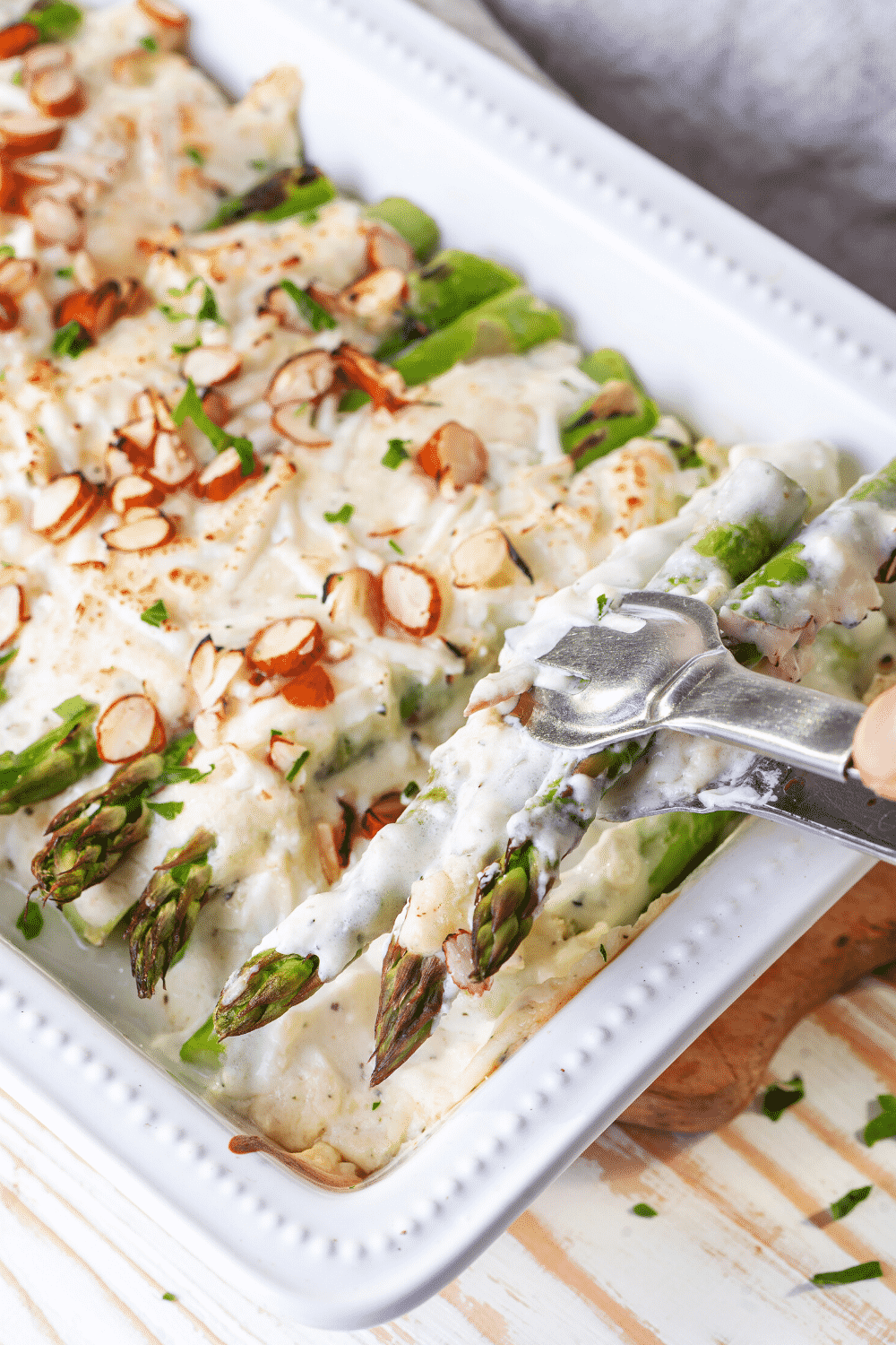 A white casserole dish filled with asparagus casserole. A fork is piercing three pieces of asparagus covered in a cream sauce and cheese.