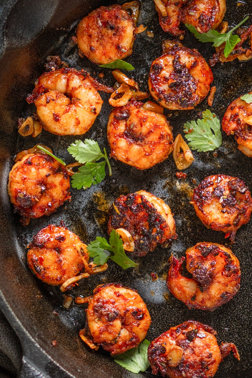 Blackened shrimp topped with fresh parsley in a cast iron pan
