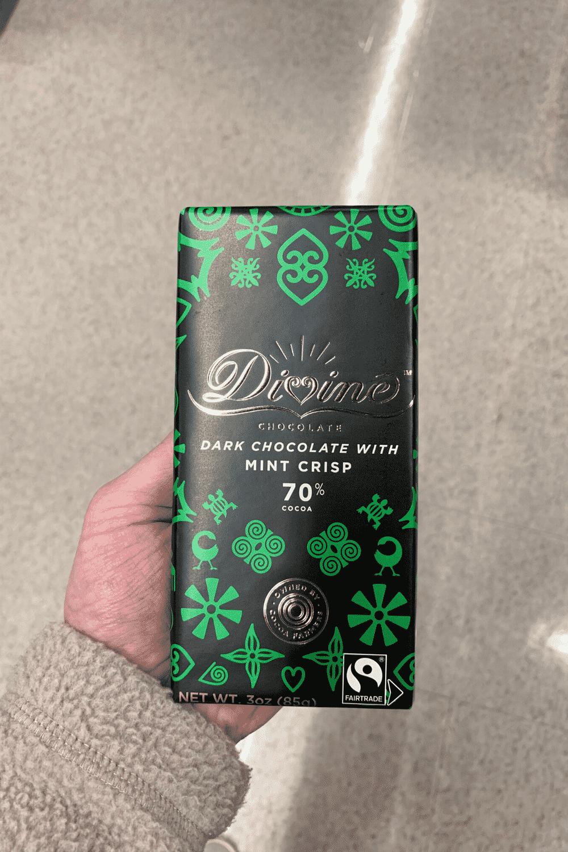 A hand holding a Divine dark chocolate with mint crisp bar