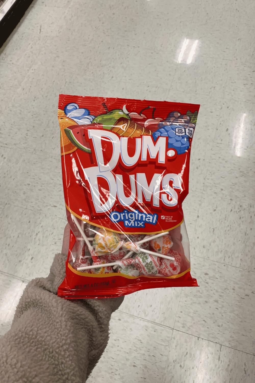 A hand holding a bag of Dum Dums original mix