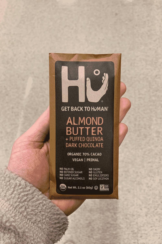 A hand holding a Hu vegan chocolate bar Almond Butter and Puffed Quinoa Dark Chocolate