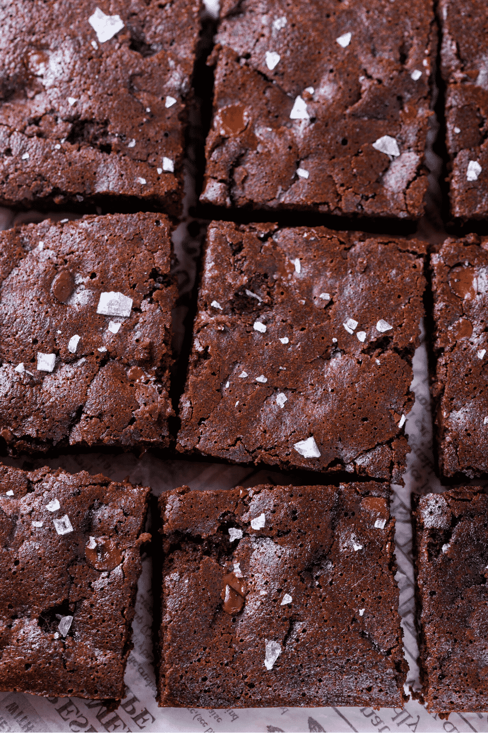 Six brownie squares on a piece of white newspaper.