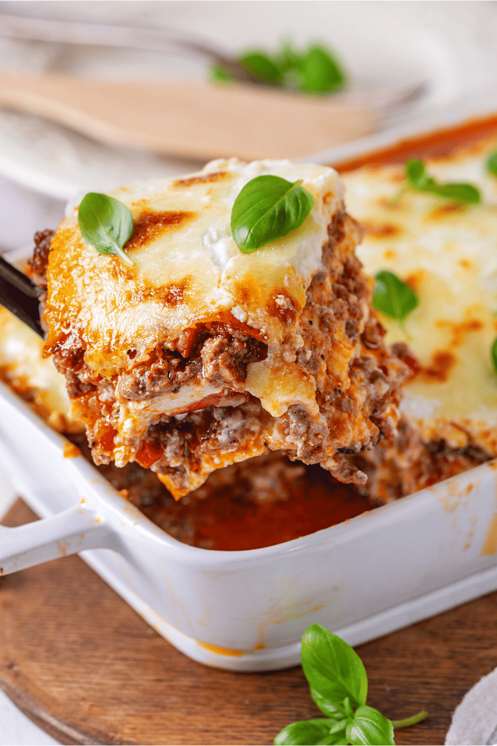 A baking dish filled with lasagna. A piece of lasagna is being taken out of the baking dish.
