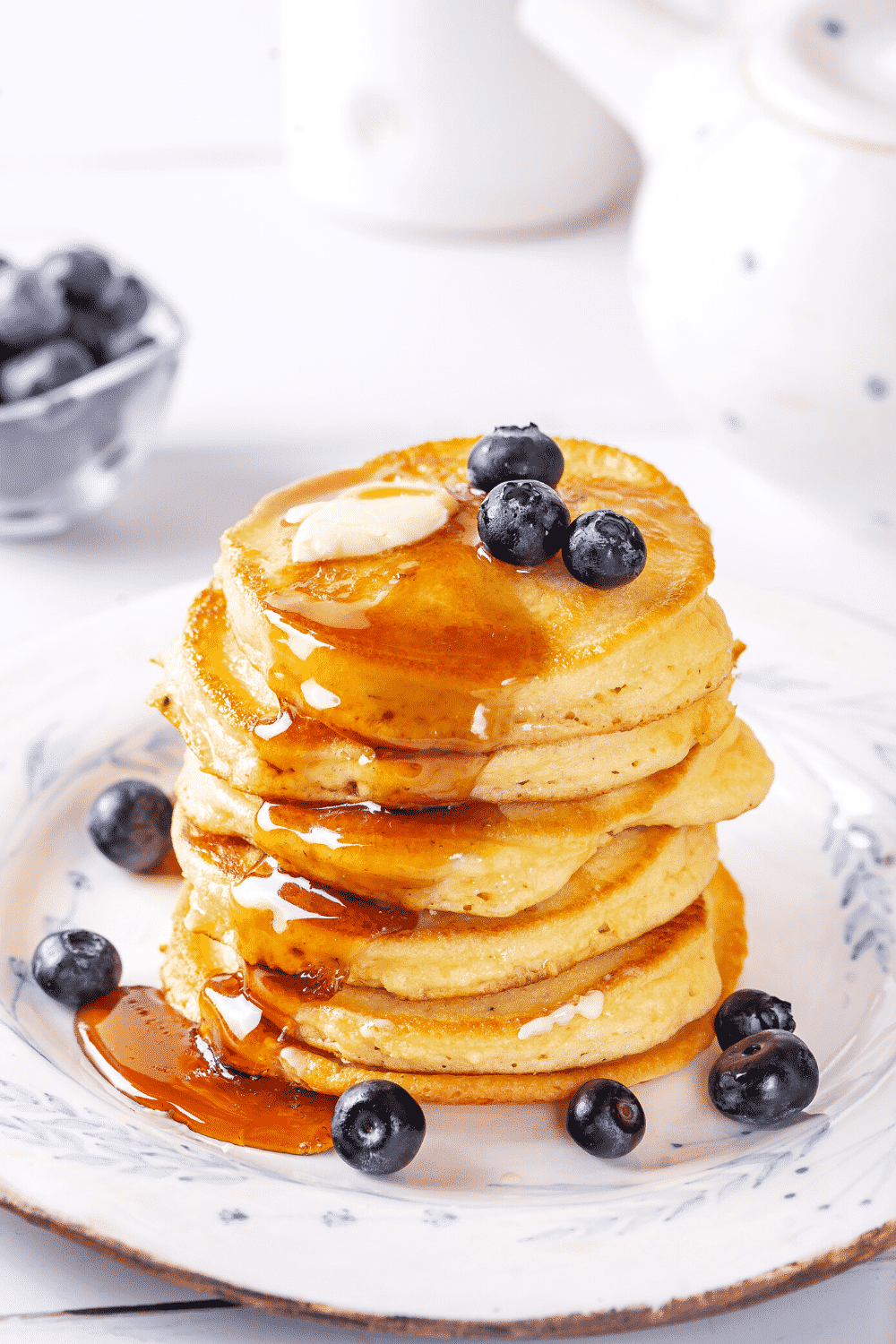 A stack of pancakes on a plate with syrup running down the front side of the stack