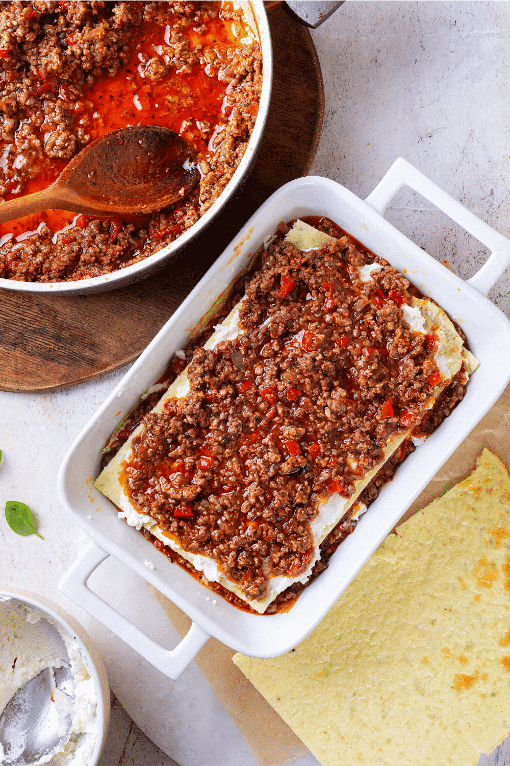 A baking dish filled with a layer of lasagna noodles and a meat sauce on the top. To the right of the dish is another lasagna noodle sheet and behind the dish is a bowl of meat sauce.