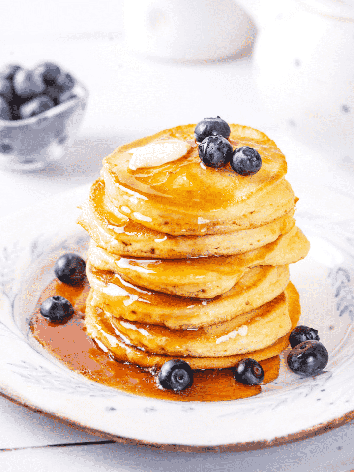 A stack of pancakes on a plate with syrup covering the front side of the pancakes and a pool of syrup on the plate