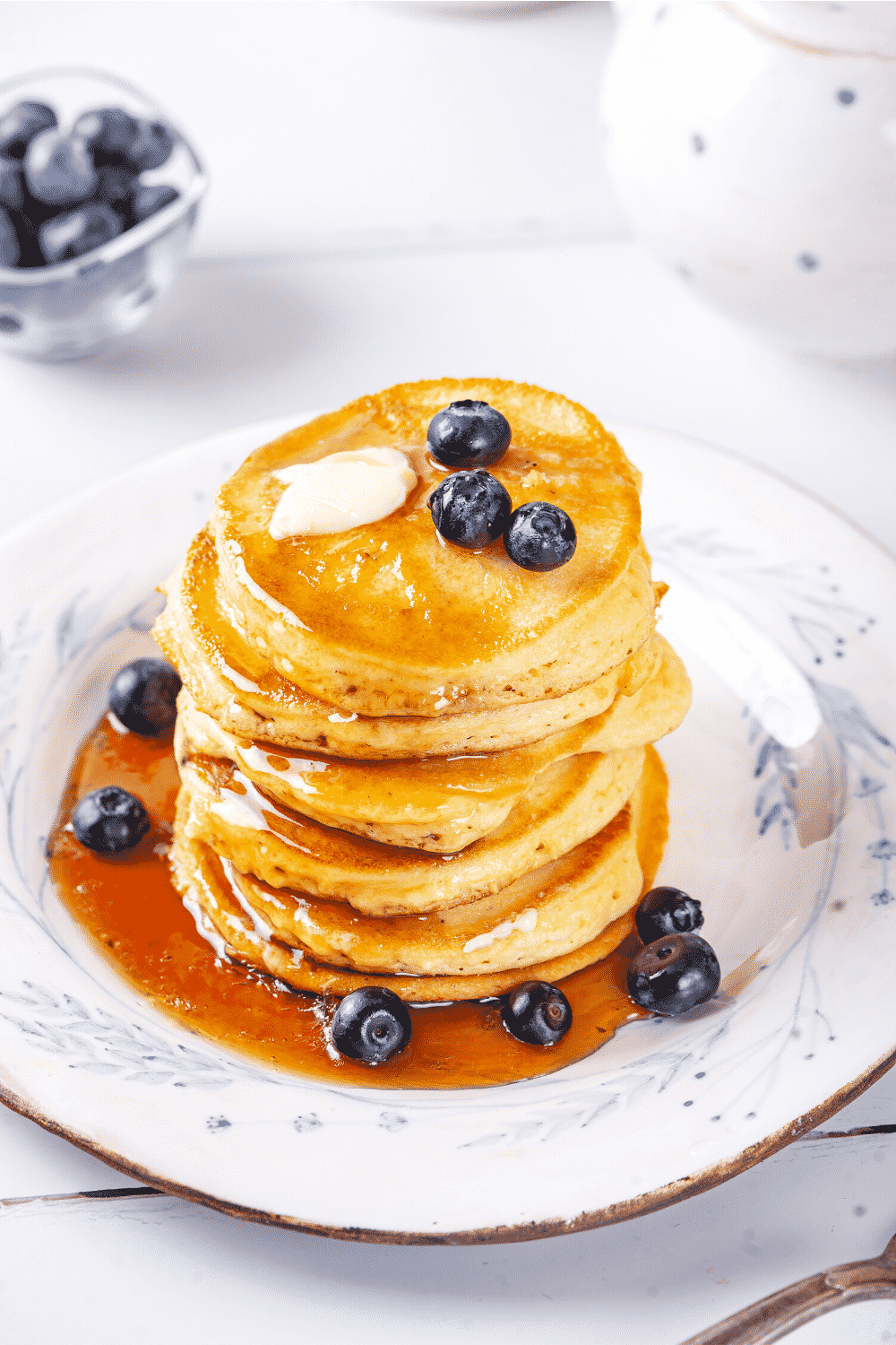 A stack of six pancakes on a white plate with some syrup on the front side of the pancakes and a pool of syrup on the front of the plate