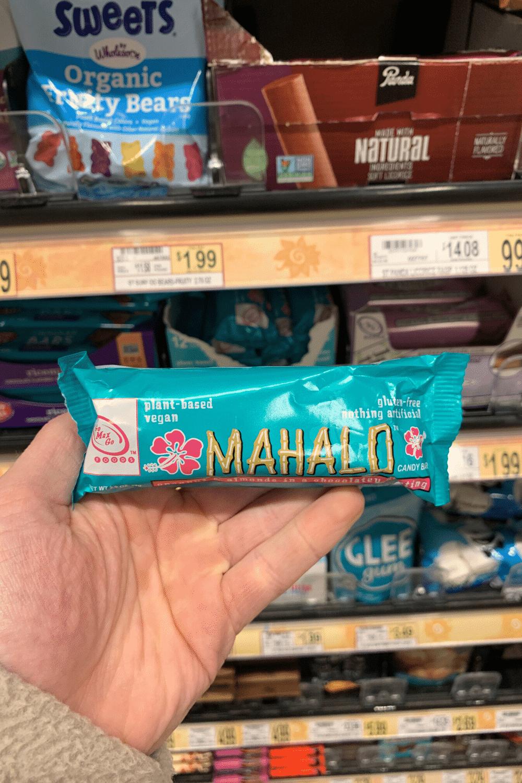 A hand holding a Mahalo vegan candy bar.