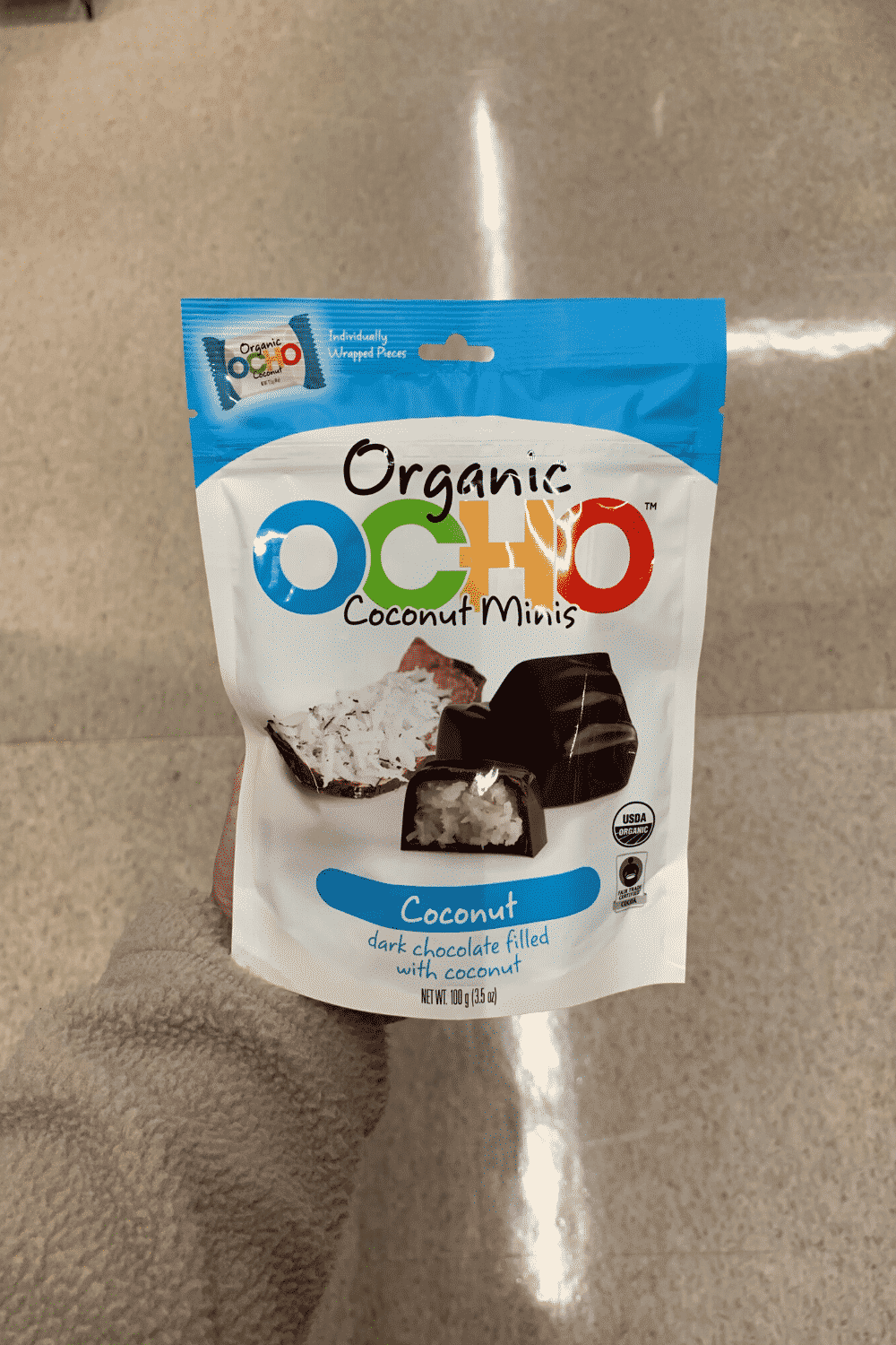 A hand holding a package of OCO coconut minis