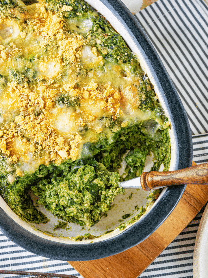 A baking dish filled with cheesy spinach casserole. A spoon is scooping out some spinach casserole from the front of the baking dish