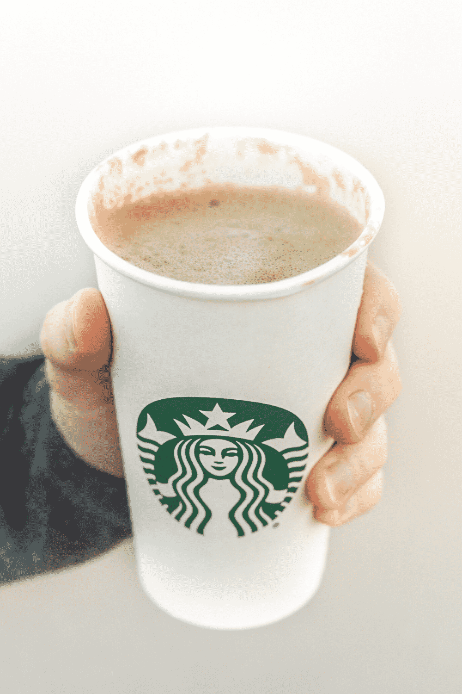 A hand holding a cup of Starbucks vegan café blonde vanilla latteA hand holding Starbucks vegan caffe blonde vanilla latte