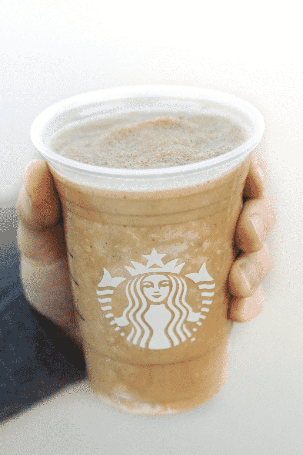 A hand holding a cup of Starbucks vegan caffe vanilla Frappuccino