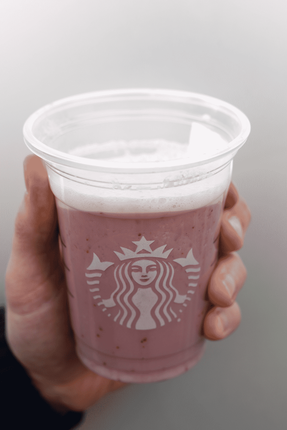 A hand holding a cup of Starbucks vegan strawberry creme Frappuccino