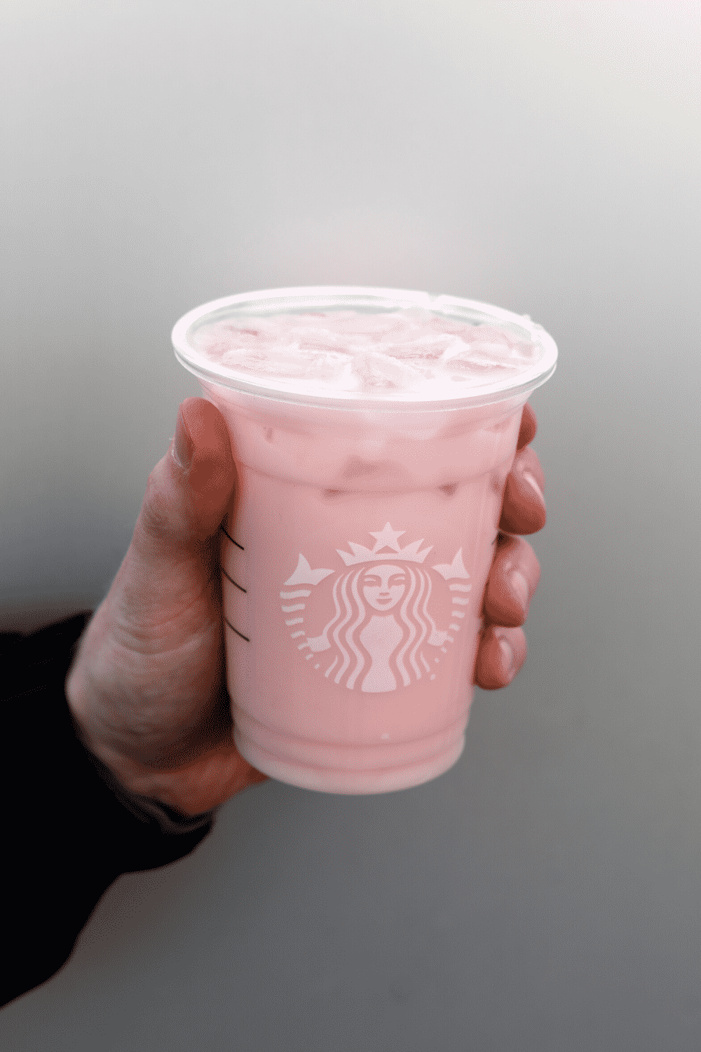 A hand holding Starbucks vegan iced guava passionfruit.