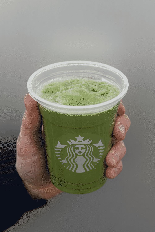 A hand holding a cup of Starbucks vegan macha green tea creme Frappuccino
