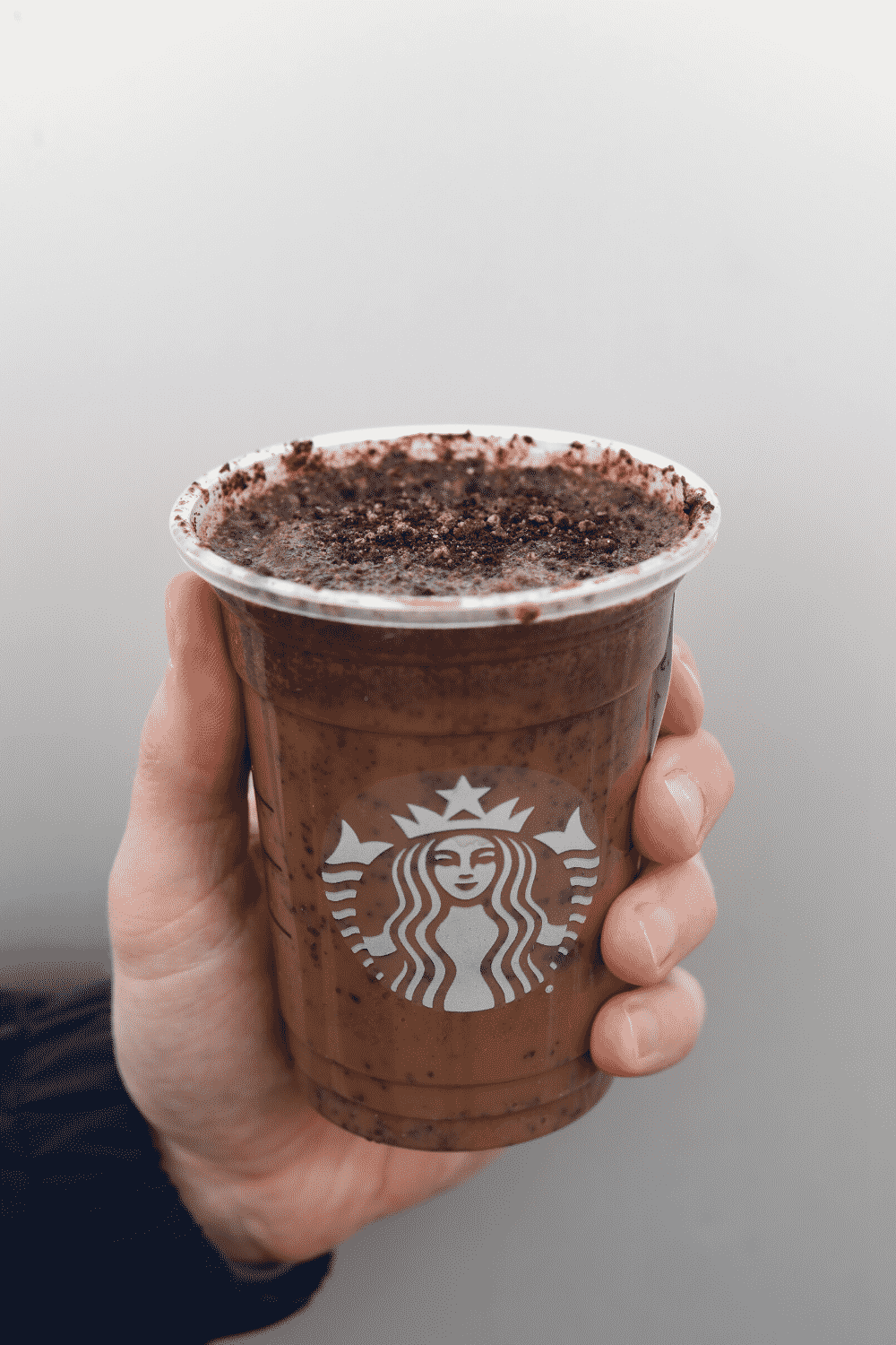 A hand holding a cup of Starbucks vegan mocha cookie crumble Frappuccino.
