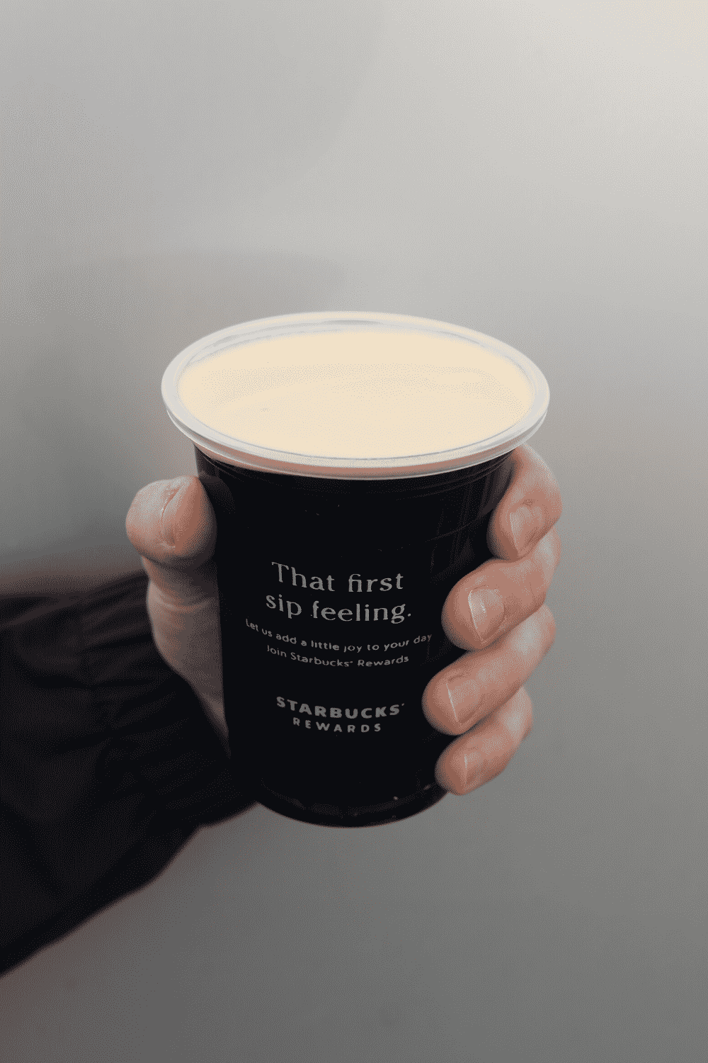 A hand holding a cup of Starbucks vegan nitro cold brew.