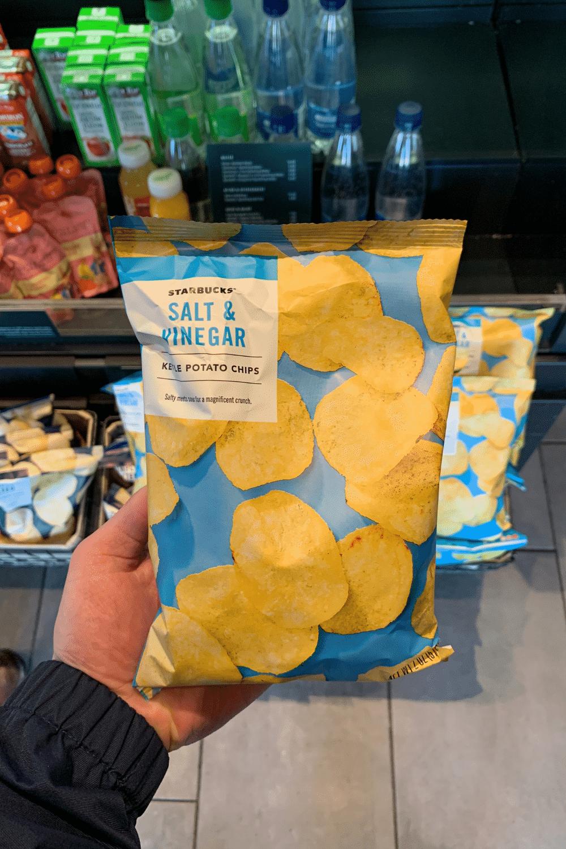 A hand holding a bag of Starbucks salt and vinegar kettle potato chips.