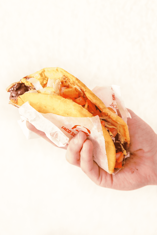 A hand holding a Taco Bell black bean Chalupa