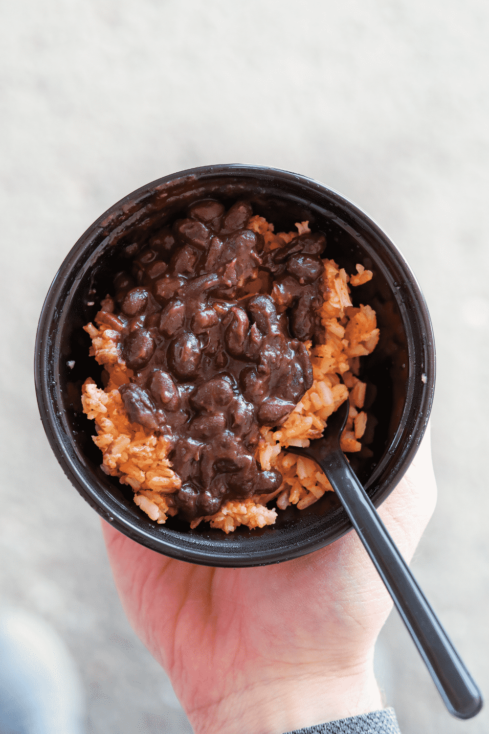 A hand holding a bowl of Taco Bell black beans and rice