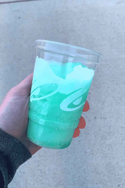 A hand holding a Taco Bell Baja Blast Freeze drink.