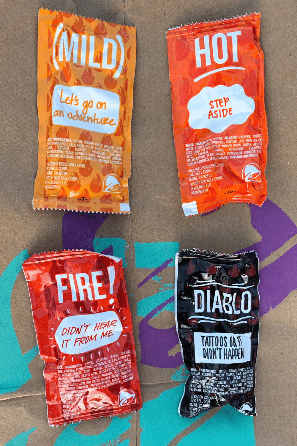 A mild, hot, fire, and diablo Taco Bell sauce packets on a brown Taco Bell bag.
