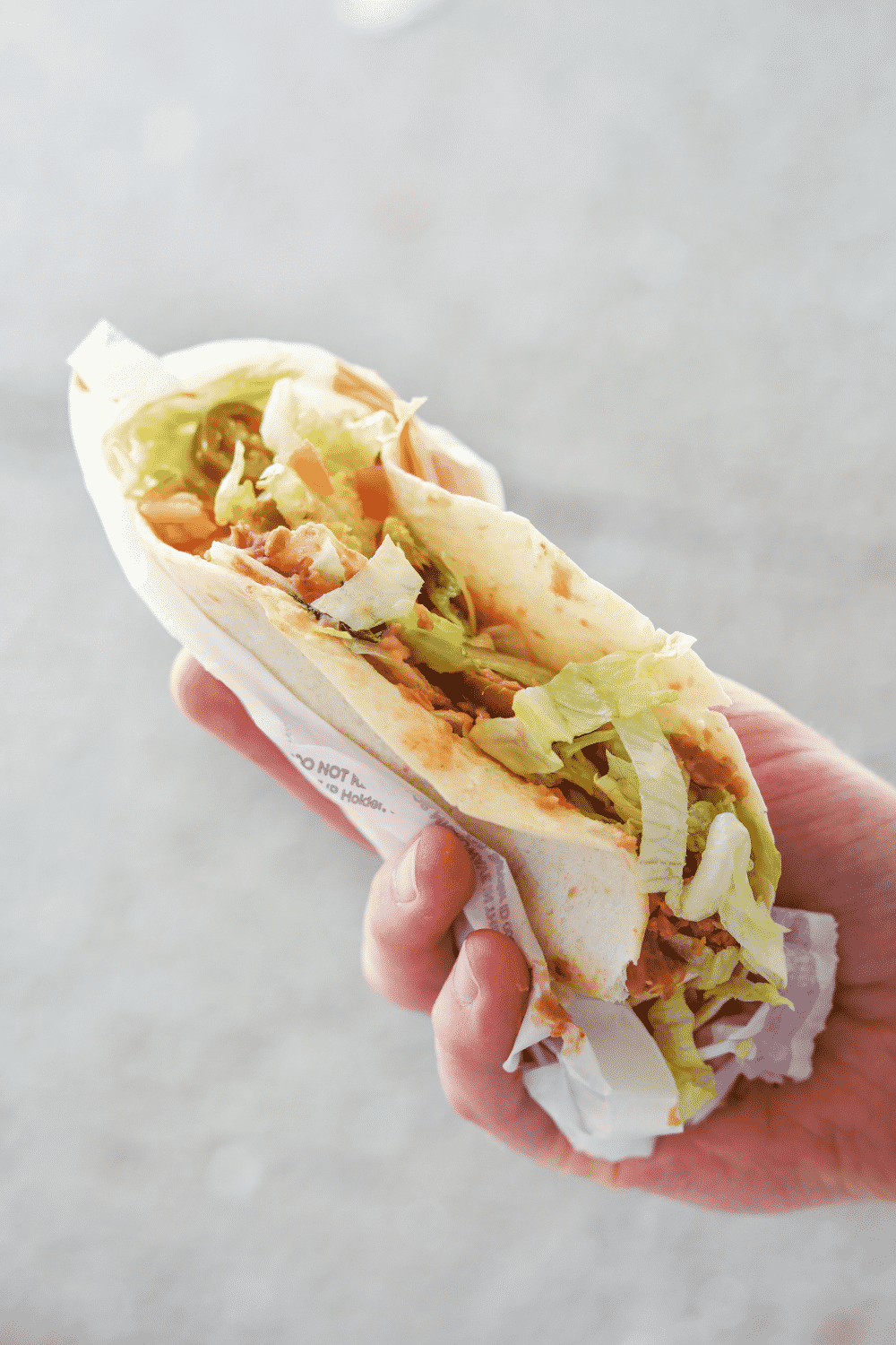 Hand holding a vegan soft taco from Taco Bell