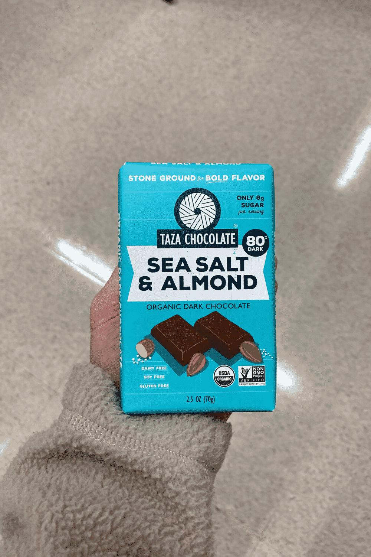 A hand holding a Taza Chocolate Sea Salt and Almond organic vegan dark chocolate bar.