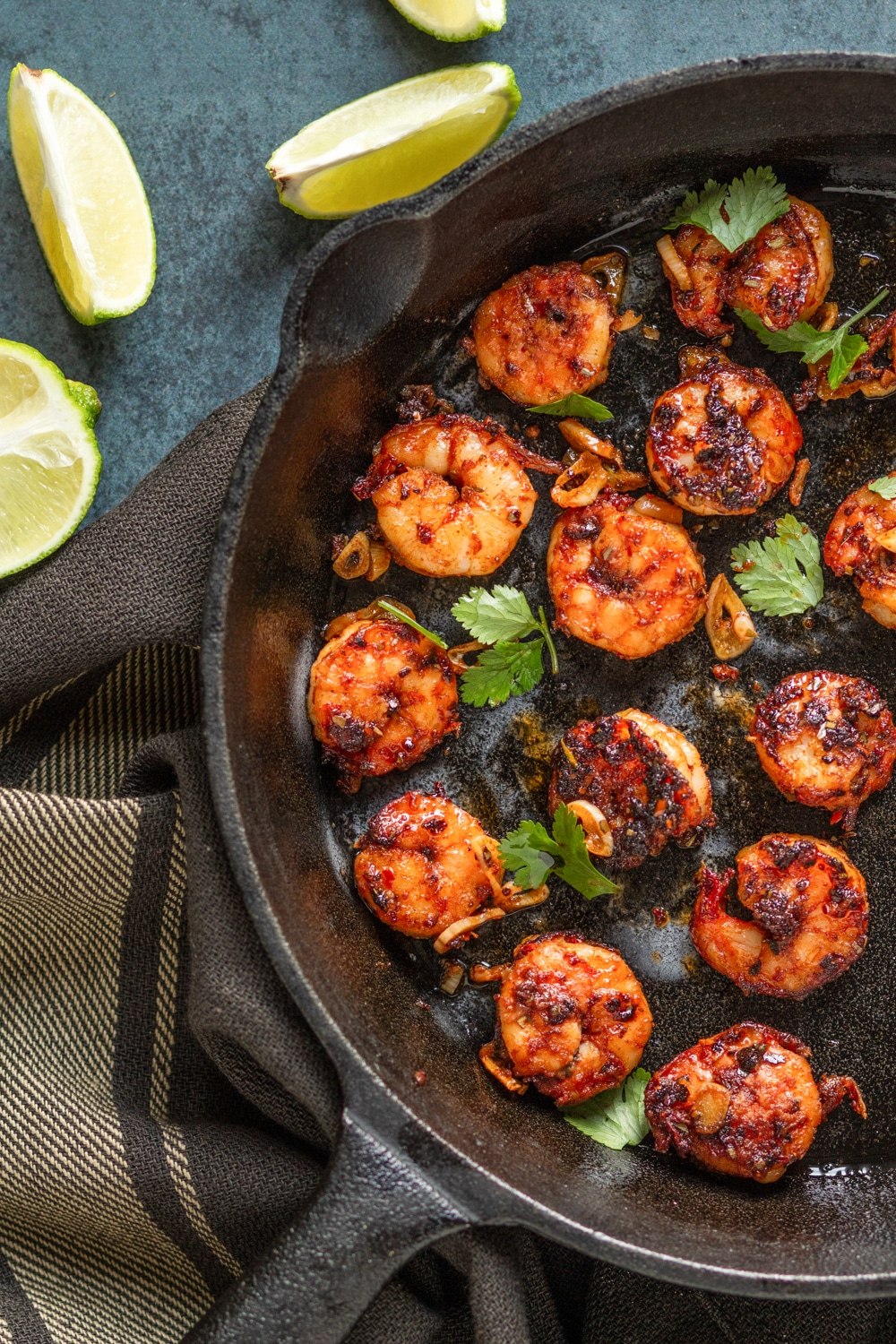 An overhead view of a skillet filled with several pieces of blackened shrimp. Below the skillet is a brown tablecloth and above that are a few slices of lime.