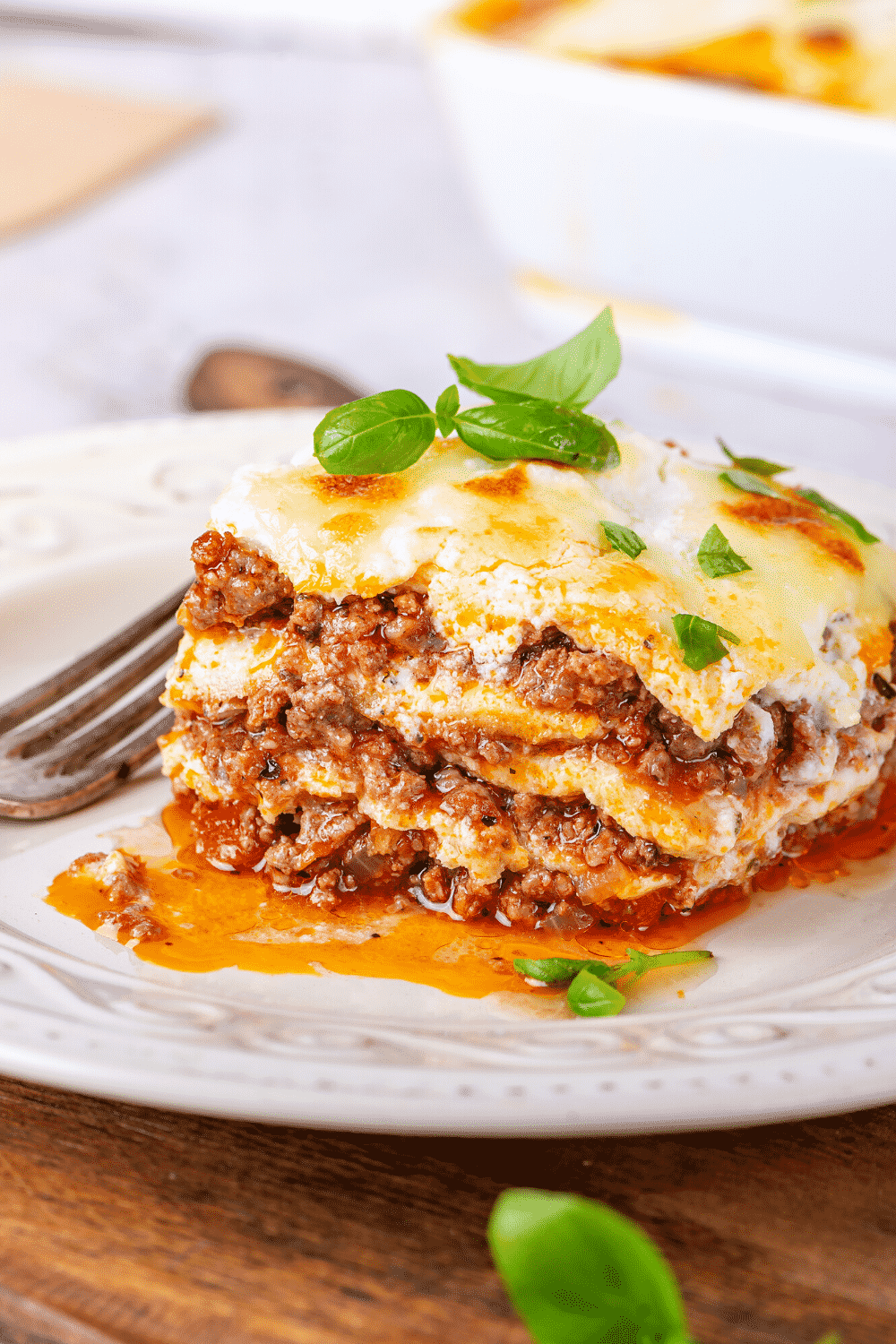 A piece of lasagna on a white plate. The white plate is on a wooden cutting board.