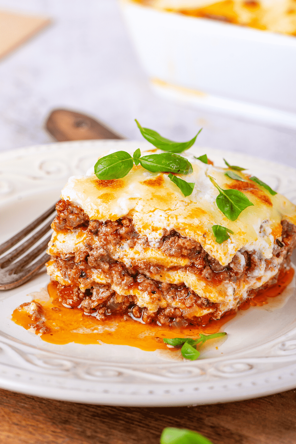 A piece of meat lasagna on a white plate. A fork is to the left of the piece of lasagna.