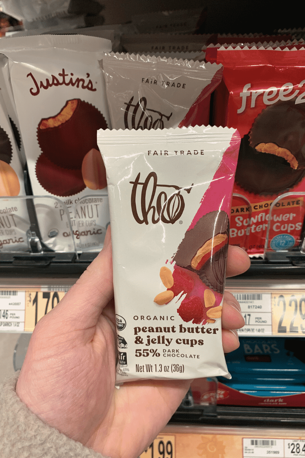 A hand holding a package of Theo peanut butter and jelly cups