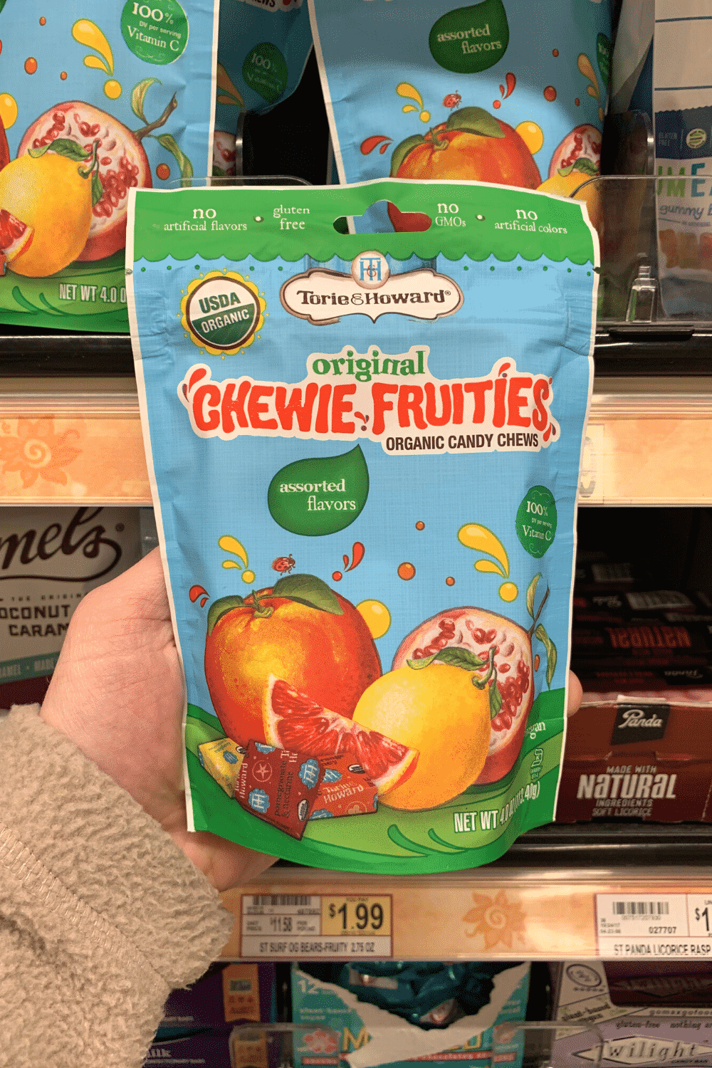 A hand holding a package of Torie and Howard original Chewie Fruities