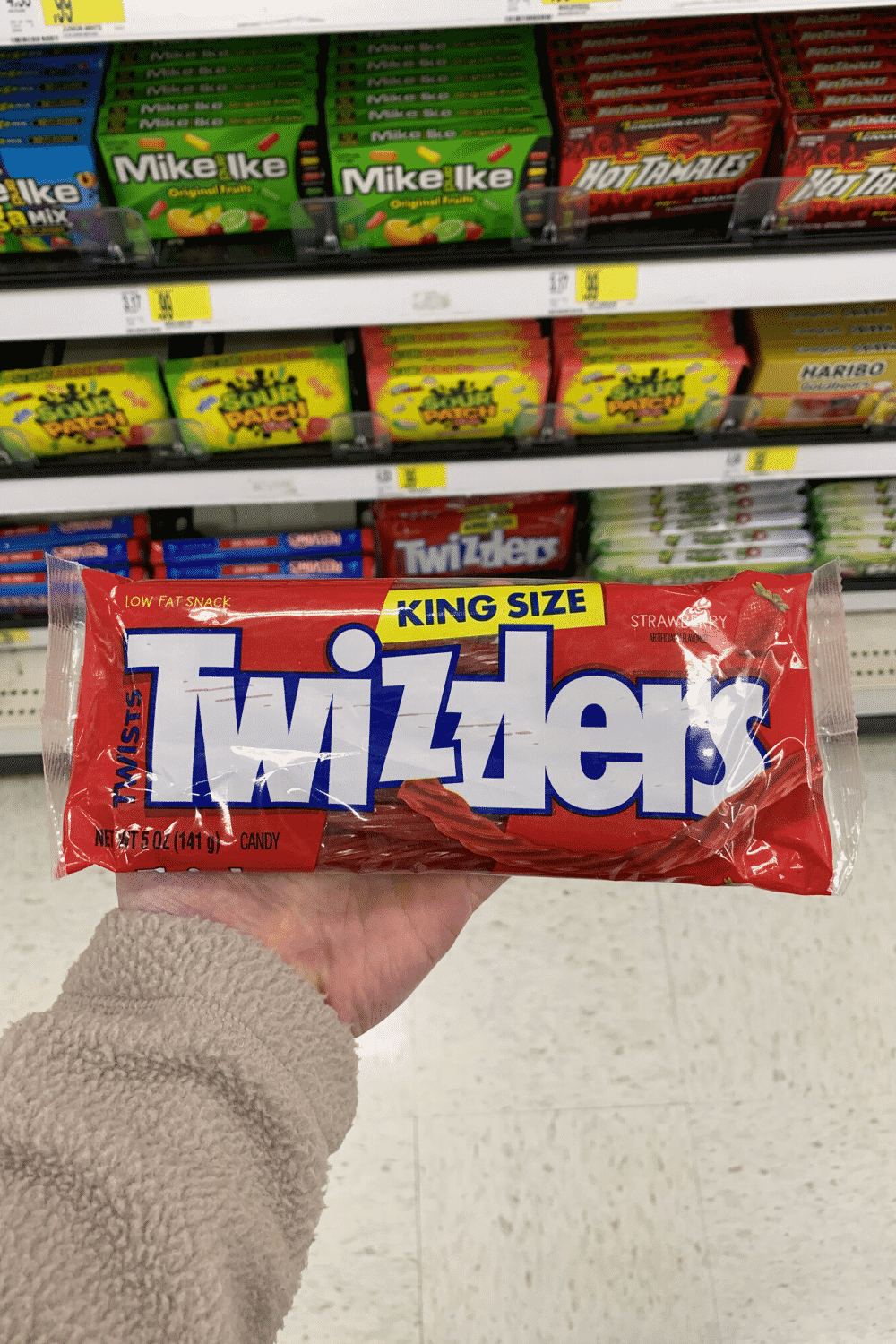 A hand holding a bag of Twizzlers