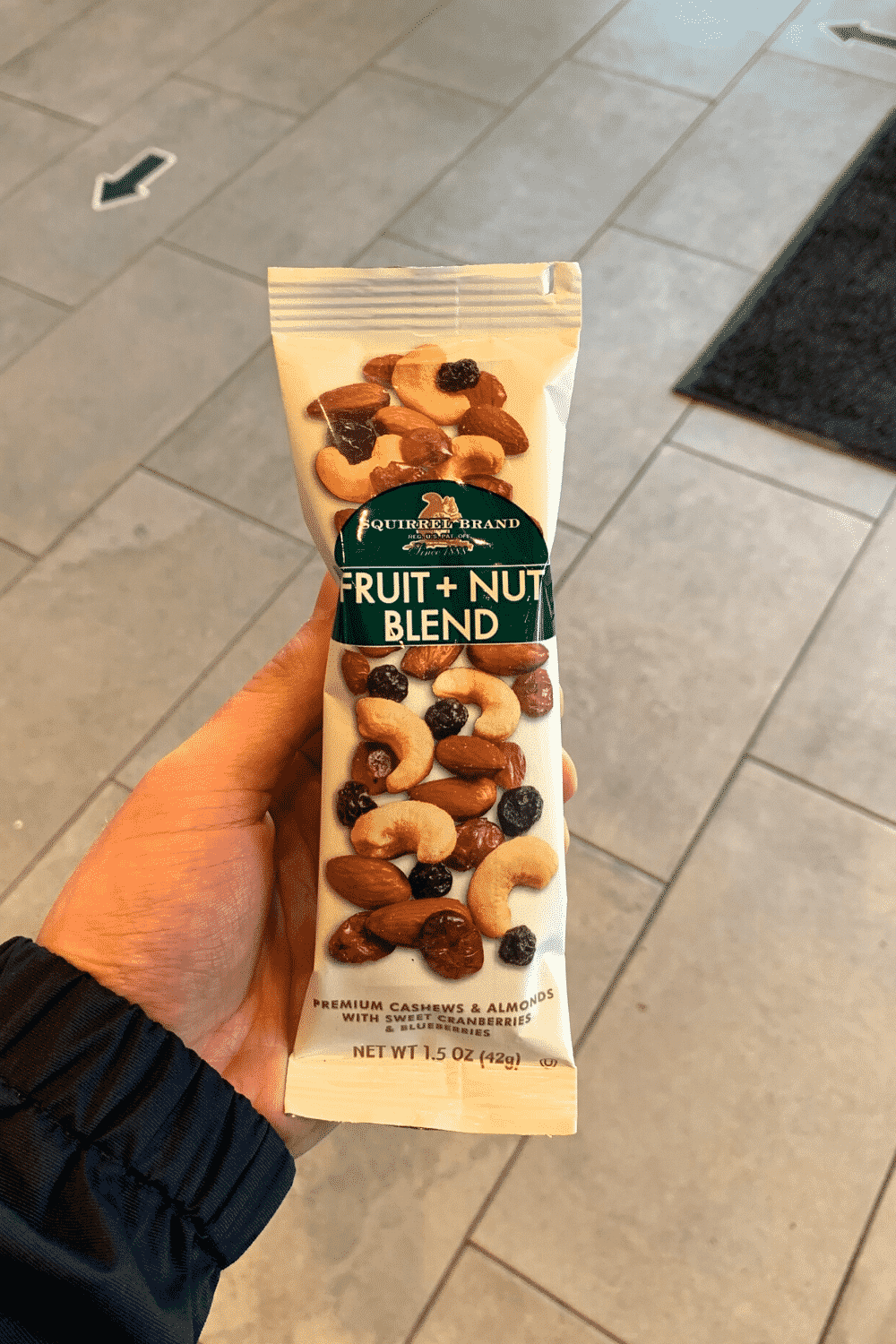 A hand holding a bag of fruit and nut blend.