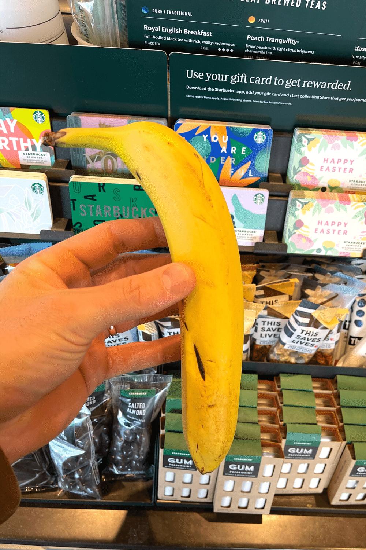 A hand holding a banana.
