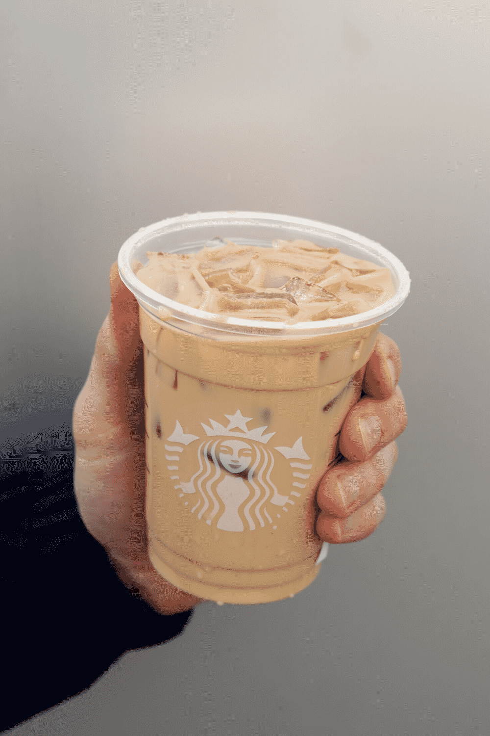 A hand holding a cup of Starbucks vegan iced cinnamon dolce latte.