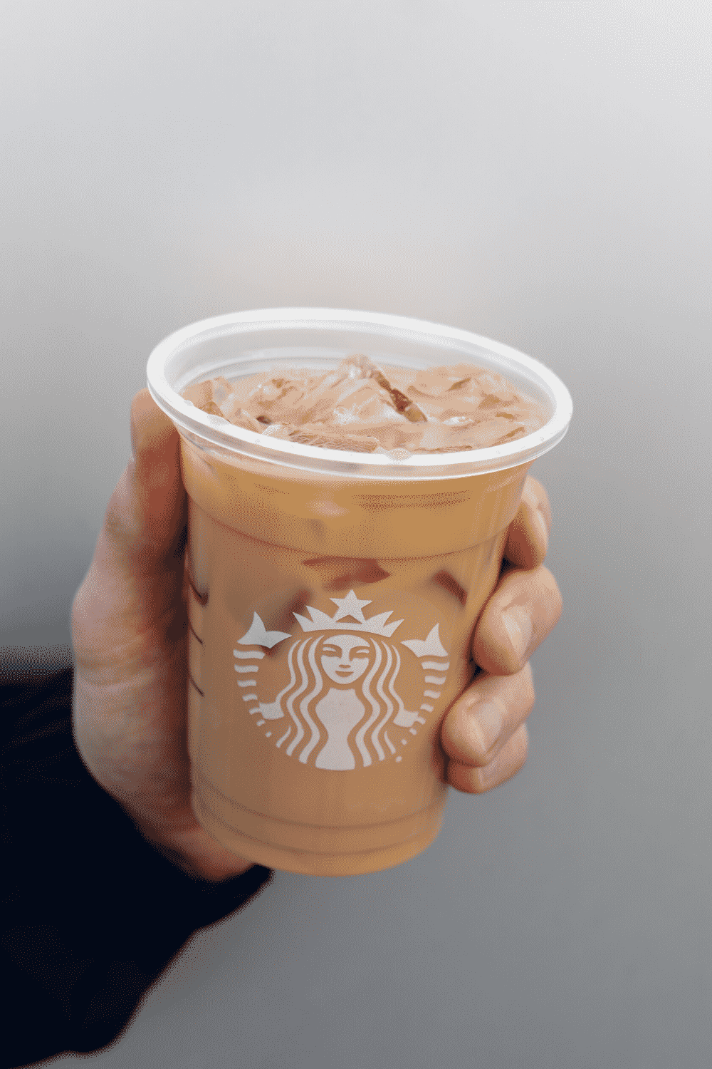 A hand holding a cup of Starbucks vegan iced coffee.