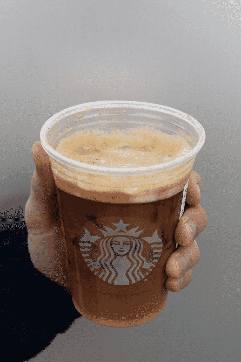 A hand holding a cup of Starbucks vegan iced shaken espresso.