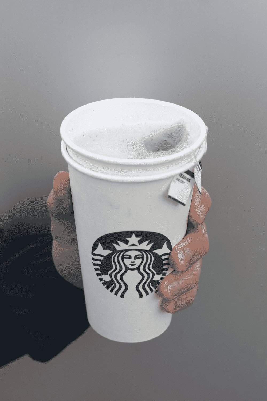 A hand holding a cup of Starbucks vegan London fog tea latte.