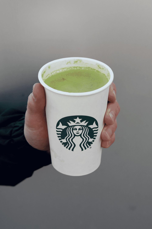 A hand holding a cup of Starbucks vegan Matcha green tea latte.