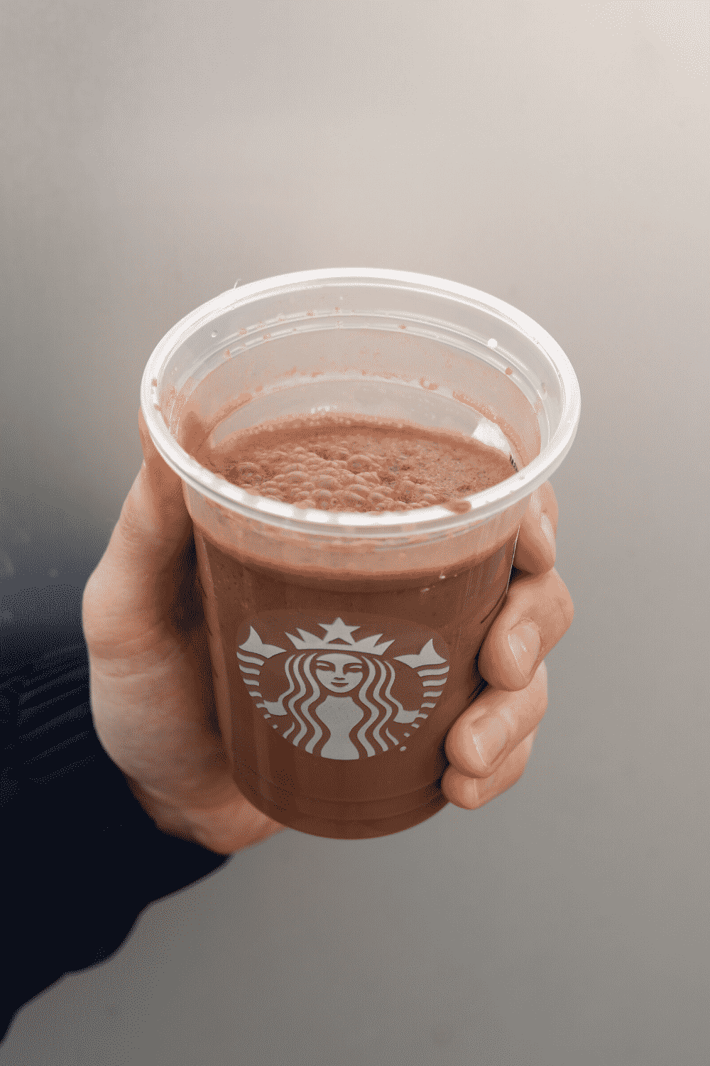 A hand holding a cup of Starbucks vegan mocha Frappuccino.