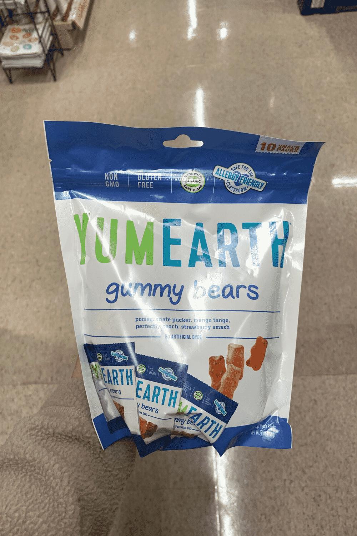 A hand holding a bag of YumEarth gummy bears