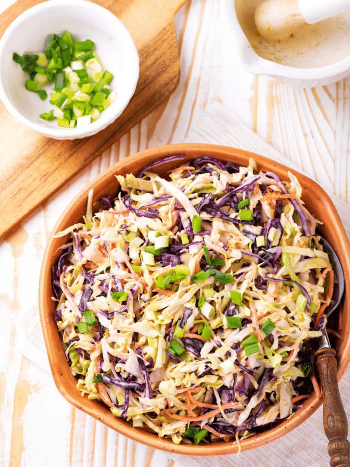 A wooden bow filled with keto coleslaw. The bowl is on a white tablecloth on top of a wooden table. Behind the bowl is a wooden cutting board with a white bowl filled with chives.