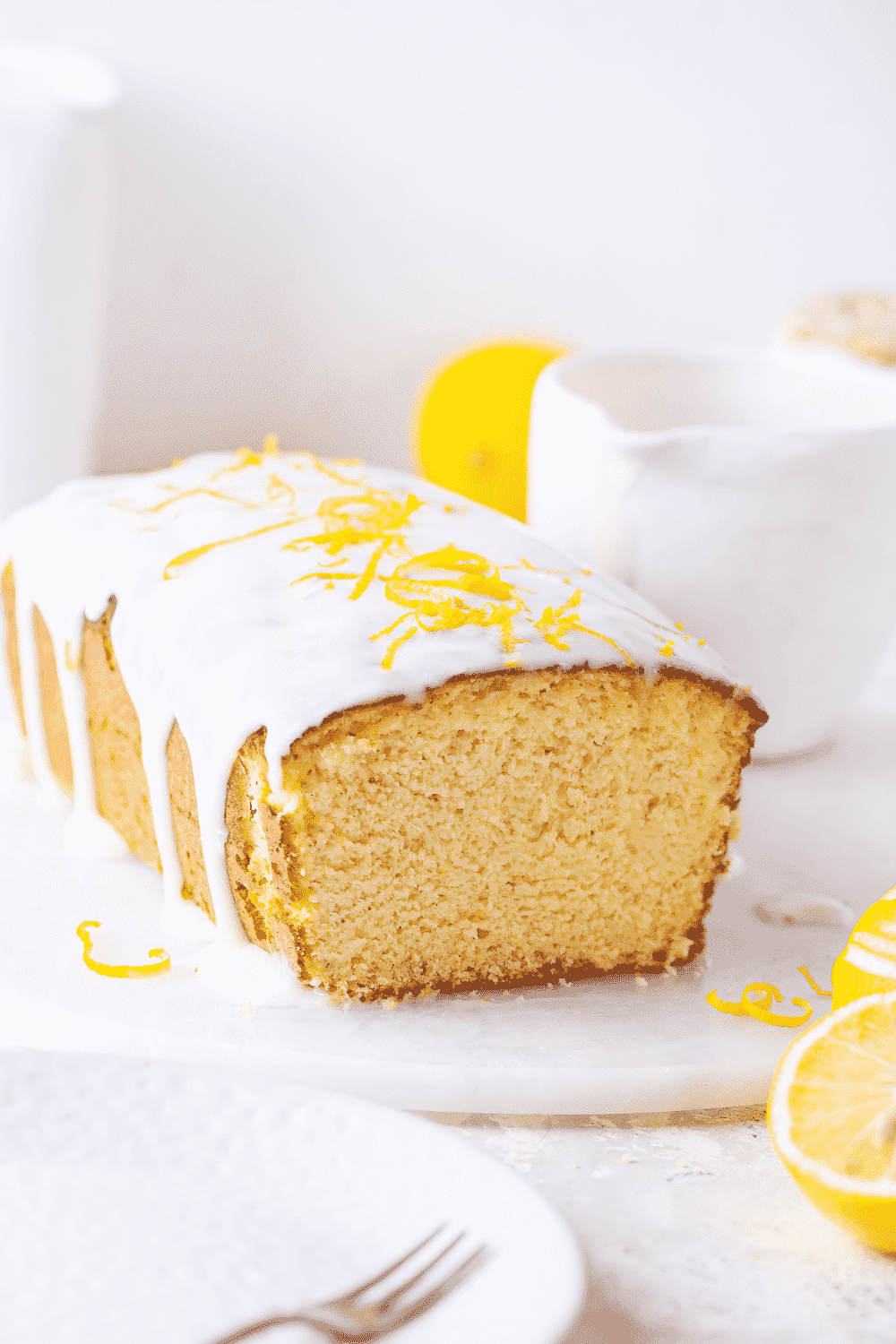 A keto lemon pound cake loaf on a white saucer. Keto glaze is dripping down the side of the keto cake. A slice is taken out of the front of the cake with the inside showing.