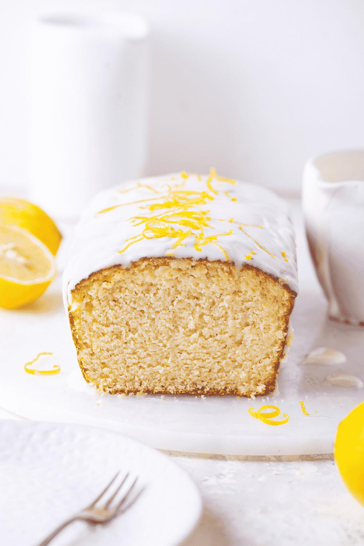 A loaf of keto lemon pound cake with a slice out of the front side of the keto cake. The keto lemon pound cake is on a white saucer on a white table.